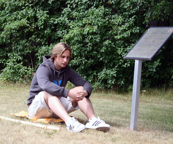 Shawn Swanky sits beside Tsilhqot'in Chiefs memorial at Quesnel.